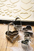 Heart-shaped biscuit cutters and cut-out biscuits