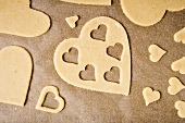 Cut-out heart-shaped biscuits on baking parchment
