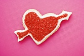 Heart-shaped biscuit with arrow, decorated with red sugar