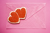 Pink envelope with red double heart-shaped biscuit
