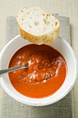 Creamed pepper soup in soup bowl, spoon & slice of baguette