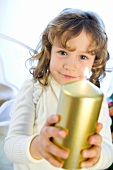 Girl dressed as angel with golden candle