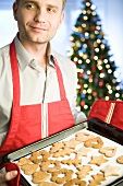 Man holding baking tray of Christmas biscuits