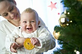 Mother holding baby with slice of orange by Christmas tree