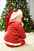 Small boy in Father Xmas costume sitting by Christmas tree