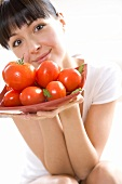 Young woman holding a bowl of tomatoes