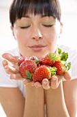 Junge Frau hält frische Erdbeeren