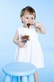 Small girl eating chocolate pudding