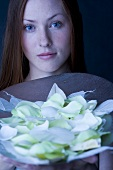 Red-haired woman holding a bowl of white rose petals