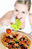 Young woman eating salad and pizza