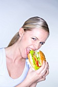 Young woman biting into a giant hamburger
