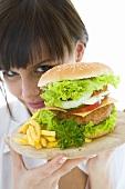 Young woman hiding behind a giant hamburger
