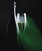 Bottle and glass of sparkling wine in green light