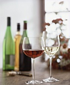 Glasses of red and white wine, wine bottles in background