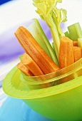 Raw carrot- and celery sticks in green bowl