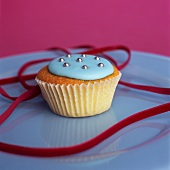 Cupcake with blue icing, silver dragees and velvet ribbon