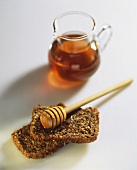 Wholegrain bread with honey and honey dipper