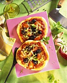 Two pizzas with tomato sauce and black olives