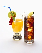 Orangeade garnished with fruit, cola with ice cubes