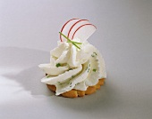 Cracker topped with soft cheese and radish