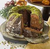 Chocolate-covered ginger cake with nuts, partly sliced