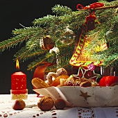 Plate of biscuits, candle, fir branch with tree ornaments