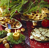 Assorted biscuits on plates under Christmas tree
