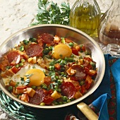 Fried eggs, sausage and vegetables in frying pan
