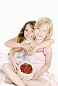 Two girls with a small basket of raspberries