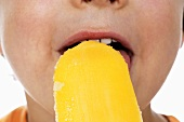 Boy eating orange ice lolly (close-up)