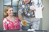 Man pouring white wine for woman