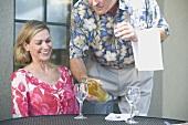Mann schenkt einer Frau Weisswein ein