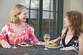 Two women with salad and wine at table on a terrace