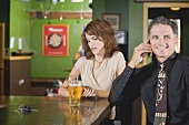 Woman looking at her watch beside man on phone in a pub
