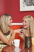 Two blond girls in café with a mobile phone