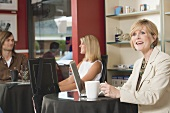 Mature woman at laptop in a café