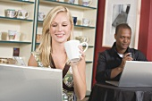 Blond woman in front of laptop in café, man in background