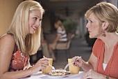 Two women in a café sharing a piece of tiramisu