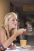 Young blond woman eating a piece of tiramisu