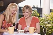 Two women at street café sharing a piece of tiramisu