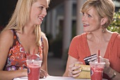 Young woman and mature woman with cold drinks, credit card