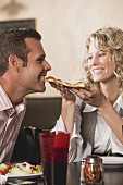 Woman feeding man pizza in restaurant