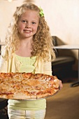 Blond girl holding a pizza