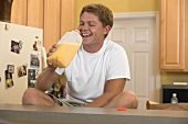 Man sitting in kitchen drinking orange juice