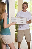 Young woman at house door receiving pizza delivery