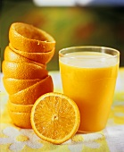 A glass of orange juice with squeezed oranges