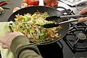 Vegetables in wok being stirred