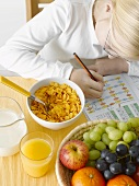Girl with exercise book in front of healthy breakfast