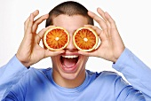 Young man holding two orange slices in front of his eyes