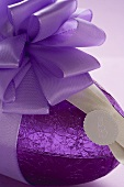A chocolate Easter egg in purple foil with purple bow